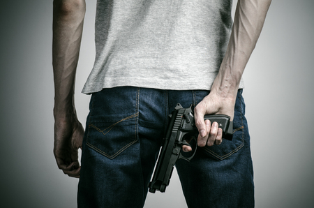 crazed: Horror and firearms topic: crazed killer with a gun on a gray background
