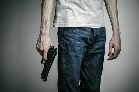 mugger: Horror and firearms topic: suicide with a gun on a gray background
