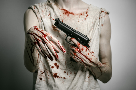 mugger: Horror and firearms topic: the bloody killer with a gun on a gray background