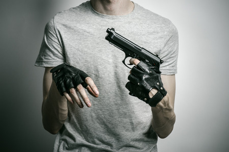 mugger: Horror and firearms topic: the killer with a gun in his hand in black gloves on a gray background Stock Photo