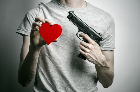 firearms: Horror and firearms topic: suicide with a gun in his hand and a red heart on a gray background