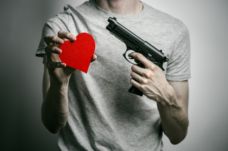 mugger: Horror and firearms topic: suicide with a gun in his hand and a red heart on a gray background