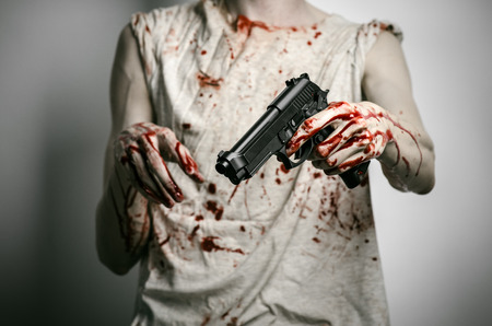 firearms: Horror and firearms topic: the bloody killer with a gun on a gray background