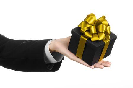ruban noir: Le thème des célébrations et des cadeaux: un homme dans un costume noir tenant un cadeau exclusif emballé dans une boîte noire avec ruban d'or et arc, le plus beau cadeau isolé sur fond blanc