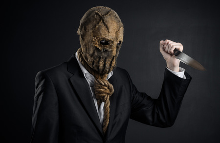 holding a knife: Fear and Halloween theme: a brutal killer in a mask holding a knife on a dark background