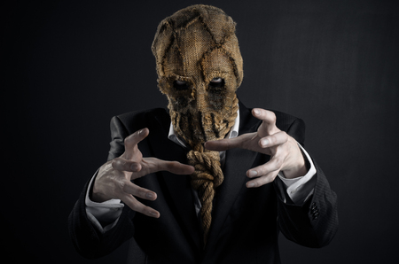 Fear and Halloween theme: a brutal killer in a mask on a dark background