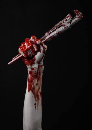 carnage: bloody hand holding an adjustable wrench, bloody key, crazy plumber, bloody theme, halloween theme, black background,isolated , bloody hand of an assassin, bloody murderer, psycho, bloody monkey wrench Stock Photo