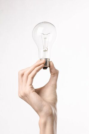 human energy: Energy consumption and energy saving topic: human hand holding a light bulb on a white background Stock Photo