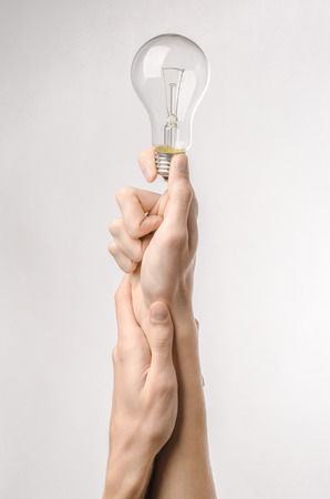 energy consumption: Energy consumption and energy saving topic: human hand holding a light bulb on a white background Stock Photo