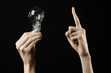 Energy consumption and energy saving topic: human hand holding a light bulb on black background Stock Photo