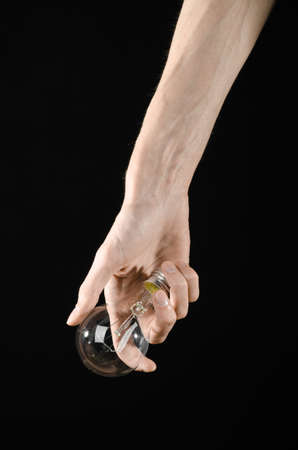 energy consumption: Energy consumption and energy saving topic: human hand holding a light bulb on black background Stock Photo