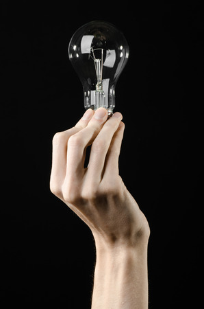 human energy: Energy consumption and energy saving topic: human hand holding a light bulb on black background Stock Photo