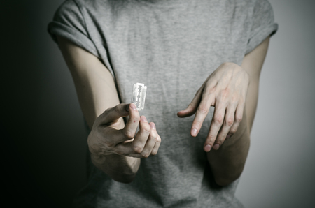 cut wrist: Depression and suicide theme: man holding a razor to suicide on a gray background