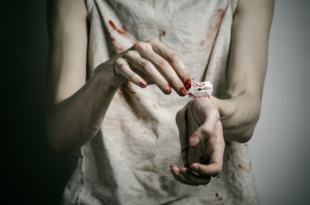 dangerous love: Depression and bloody Halloween theme: a man holding a bloody razor for suicide on a gray background