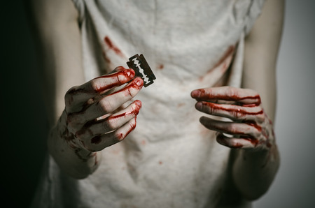 failed attempt: Depression and bloody Halloween theme: a man holding a bloody razor for suicide on a gray background