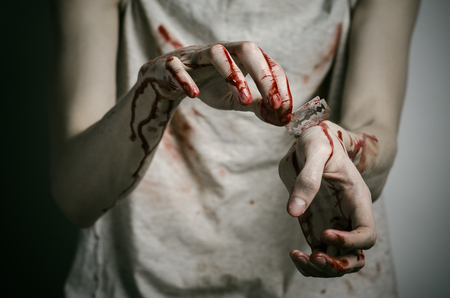 cut wrist: Depression and bloody Halloween theme: a man holding a bloody razor for suicide on a gray background