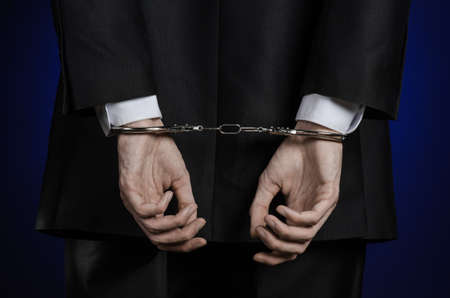 detained: Corruption and bribery theme: businessman in a black suit with handcuffs on his hands on a dark blue background isolated view from the back Stock Photo