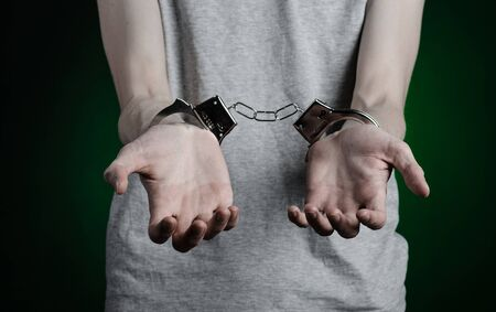 Prison and convicted topic: man with handcuffs on his hands in a gray T-shirt and blue jeans on a dark green background, put handcuffs on the drug dealer Stock Photo