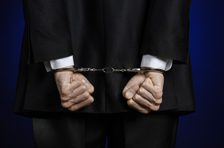 venality: Corruption and bribery theme: businessman in a black suit with handcuffs on his hands on a dark blue background isolated view from the back Stock Photo