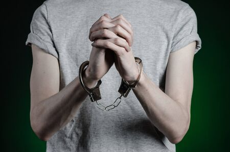 drug dealer: Prison and convicted topic: man with handcuffs on his hands in a gray T-shirt and blue jeans on a dark green background, put handcuffs on the drug dealer Stock Photo