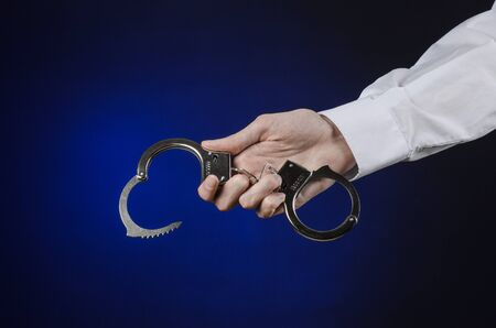 manacle: Dishonest and a prison doctor topic: the hand of man in a white shirt with handcuffs on a dark blue background, put handcuffs on the doctor, the illegal sale of organs Stock Photo