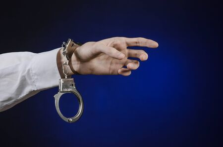 conman: Dishonest and a prison doctor topic: the hand of man in a white shirt with handcuffs on a dark blue background, put handcuffs on the doctor, the illegal sale of organs Stock Photo