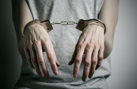rapist: Prison and convicted topic: man with handcuffs on his hands in a gray T-shirt on a gray background, put handcuffs on rapist