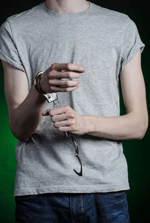 manacle: Prison and convicted topic: man with handcuffs on his hands in a gray T-shirt and blue jeans on a dark green background, put handcuffs on the drug dealer Stock Photo