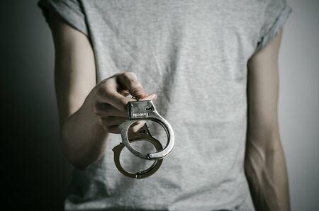 put in prison: Prison and convicted topic: man with handcuffs on his hands in a gray T-shirt on a gray background, put handcuffs on rapist