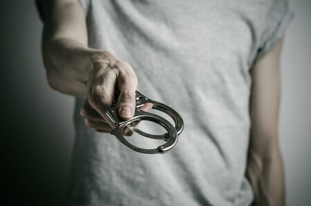 Prison and convicted topic: man with handcuffs on his hands in a gray T-shirt on a gray background, put handcuffs on rapist