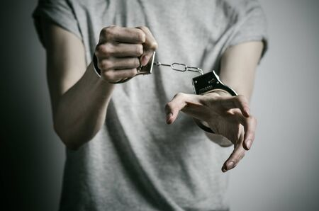 convicted: Prison and convicted topic: man with handcuffs on his hands in a gray T-shirt on a gray background, put handcuffs on rapist