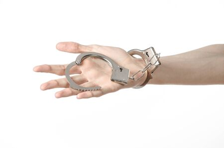 put in prison: Prison and convicted topic: man hands with handcuffs isolated on white background in studio, put handcuffs on killer studio Stock Photo