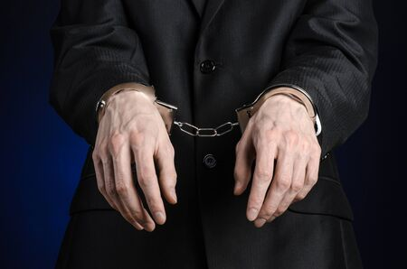 incarceration: Corruption and bribery theme: businessman in a black suit with handcuffs on his hands on a dark blue background isolated