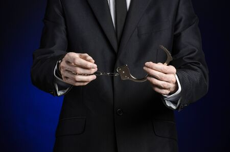 venality: Corruption and bribery theme: businessman in a black suit with handcuffs on his hands on a dark blue background isolated