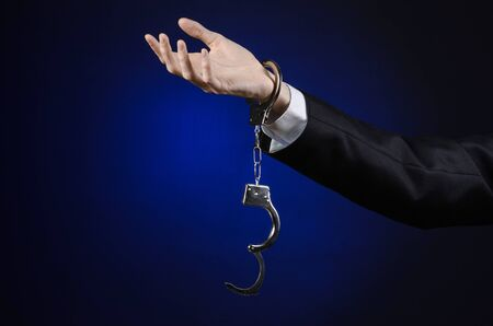 felony: Corruption and bribery theme: businessman in a black suit with handcuffs on his hands on a dark blue background isolated