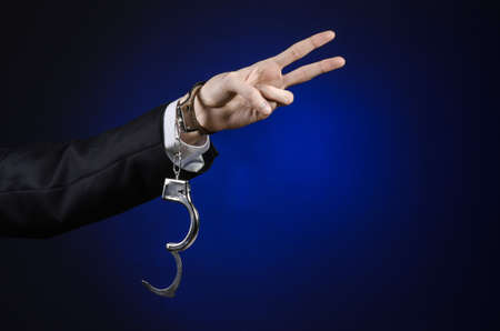 detained: Corruption and bribery theme: businessman in a black suit with handcuffs on his hands on a dark blue background isolated
