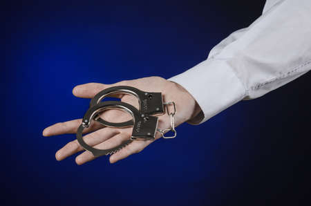 put in prison: Dishonest and a prison doctor topic: the hand of man in a white shirt with handcuffs on a dark blue background, put handcuffs on the doctor, the illegal sale of organs Stock Photo
