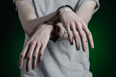put in prison: Prison and convicted topic: man with handcuffs on his hands in a gray T-shirt and blue jeans on a dark green background, put handcuffs on the drug dealer Stock Photo
