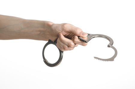 incarceration: Prison and convicted topic: man hands with handcuffs isolated on white background in studio, put handcuffs on killer studio Stock Photo