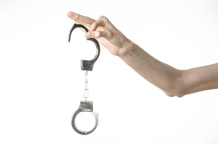 convicted: Prison and convicted topic: man hands with handcuffs isolated on white background in studio, put handcuffs on killer studio Stock Photo