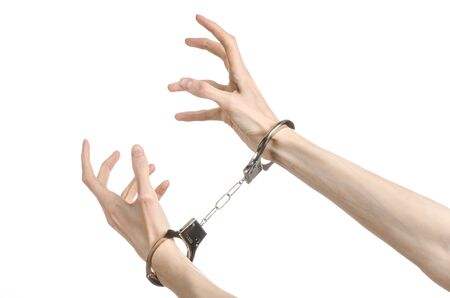 Prison and convicted topic: man hands with handcuffs isolated on white background in studio, put handcuffs on killer studio Stock Photo