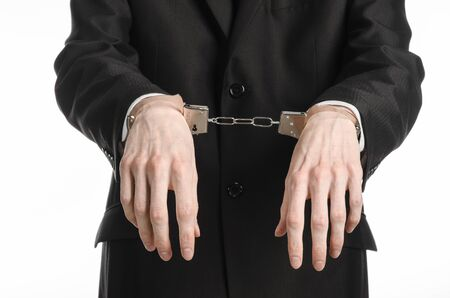 incarceration: Corruption and bribery theme: businessman in a black suit with handcuffs on his hands on a white background isolated