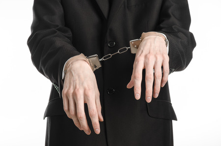 manacle: Corruption and bribery theme: businessman in a black suit with handcuffs on his hands on a white background isolated