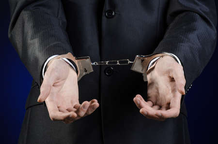manacle: Corruption and bribery theme: businessman in a black suit with handcuffs on his hands on a dark blue background isolated