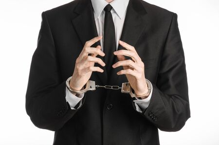 venality: Corruption and bribery theme: businessman in a black suit with handcuffs on his hands on a white background isolated