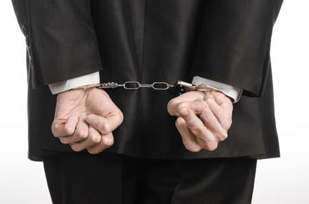 detained: Corruption and bribery theme: businessman in a black suit with handcuffs on his hands on a white background isolated