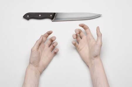 carnage: Murder and Halloween theme: A mans hand reaching for a knife, a human hand holding a knife isolated on a gray background from above Stock Photo