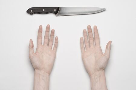 holding a knife: Murder and Halloween theme: A mans hand reaching for a knife, a human hand holding a knife isolated on a gray background from above Stock Photo