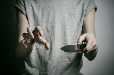 carnage: Murder and Halloween theme: a man holding a knife on a gray background studio