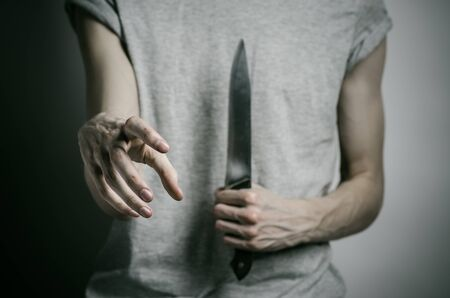 holding a knife: Murder and Halloween theme: a man holding a knife on a gray background studio